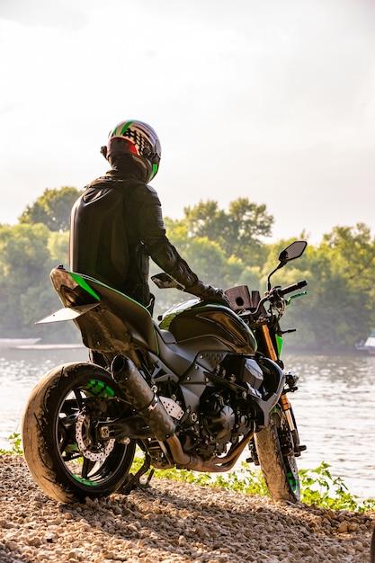 Bemannen sie den tragenden motorradsturzhelm und sicherheitsuniform, die draußen auf fahrrad, schöne szenische landschaft sitzen Premium Fotos