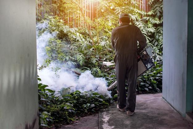 Bemannen sie die arbeit, die einnebelt, um moskito für das verhindern des verbreiteten dengue-fiebers und des zika-virus zu beseitigen Premium Fotos