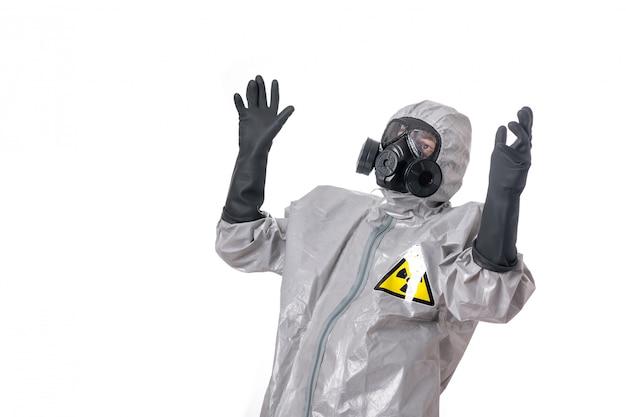Bemannen sie die aufstellung in einem grauen schutzanzug mit einem gelben strahlungszeichen, mit einer schutzgasmaske Premium Fotos