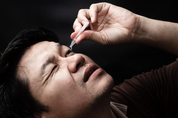 Bemannen sie die fallende augentropfenmedizin, die seine augenschmerzen mit schwarzem hintergrund heilt Kostenlose Fotos
