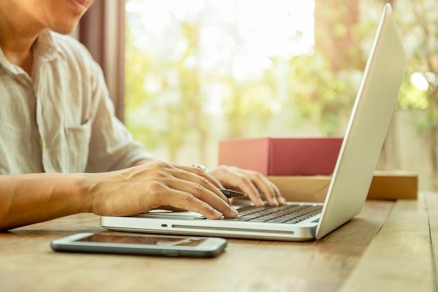 Bemannen sie die hände, die auf laptoptastatur mit paketpaketlieferung auf tabelle schreiben. Premium Fotos
