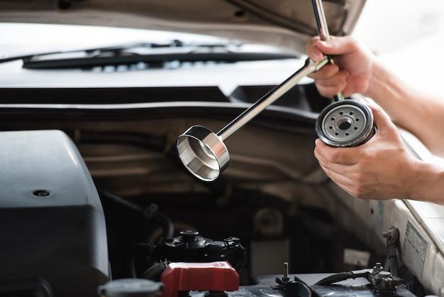 Bemannen sie die hände, die den ölfilterkappenschlüssel und automobilölfilter halten, die sich vorbereiten zu ändern. Premium Fotos
