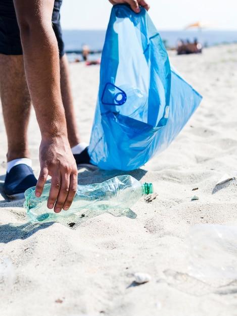 Bemannen sie die hand, die abfallplastikflasche durch den strand beim halten der blauen abfalltasche aufhebt Kostenlose Fotos