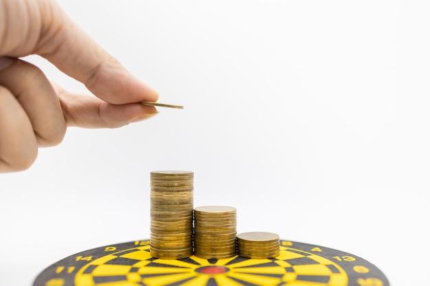 Bemannen sie die hand, die eine münze hält und zur oberseite des stapels münzen auf dartscheibe sich setzt. Premium Fotos