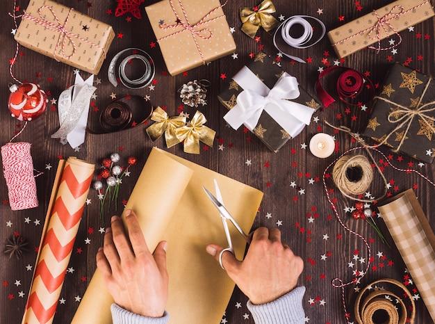 Bemannen sie die hand, die rolle des kraftpapiers mit scheren für den schnitt der verpackungsweihnachtsgeschenkbox hält Kostenlose Fotos