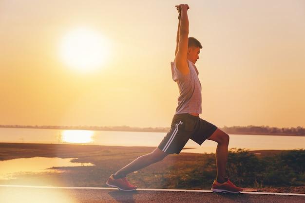 Bemannen sie die läuferathleten, die oben für übung im freien mit sonnenunterganghintergrund entwurmieren Premium Fotos