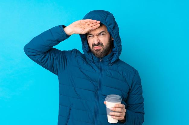 Bemannen sie die tragende winterjacke und das halten eines mitnehmerkaffees über lokalisierter blauer wand mit müdem und krankem ausdruck Premium Fotos
