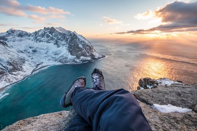 Bemannen sie die wandererquerbeine, die auf höchstberg mit küstenlinie bei sonnenuntergang sitzen Premium Fotos