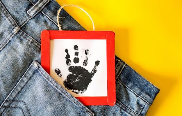 Bemannen sie jeansdetail mit handgemachtem rahmen mit einer gestempelten kinderhand in der tasche Premium Fotos