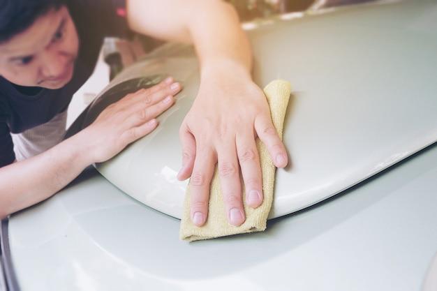 Bemannen sie sauberes und wachsen sie das auto - auto-wartungsservicekonzept im freien Kostenlose Fotos