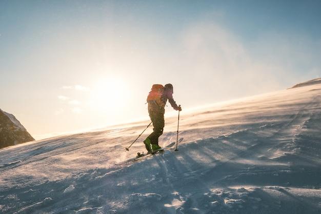 Bemannen sie skifahrer mit dem rucksacktrekking auf schneeberg mit sonnenlicht Premium Fotos