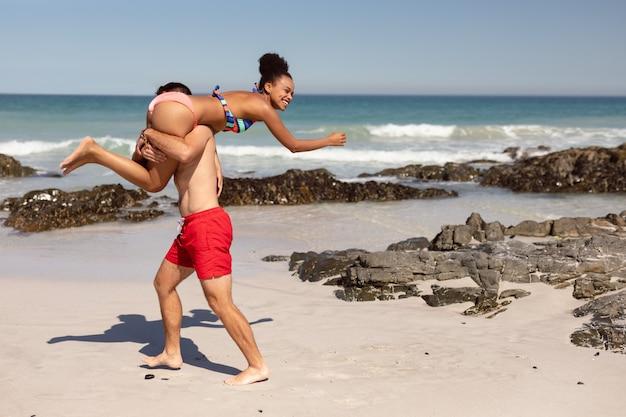 Bemannen sie tragende frau auf schultern am strand im sonnenschein Kostenlose Fotos
