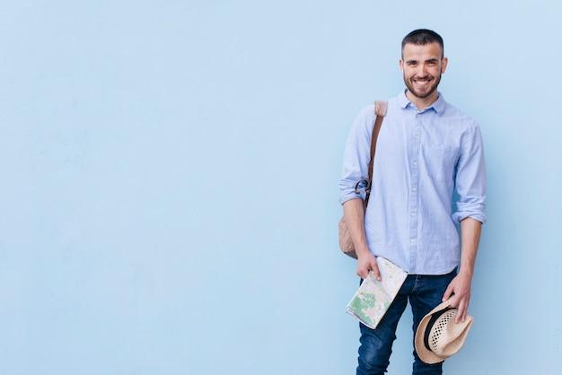 Bemannen sie tragetasche mit dem halten der karte und des hutes gegen blaue hintergrundwand Premium Fotos