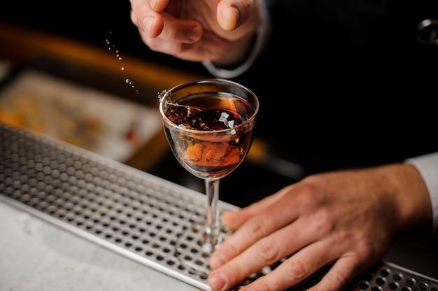 Bemannt die hand, die ein glas mit dem spritzen des alkoholischen getränks mit einer scheibe der orange hält Premium Fotos