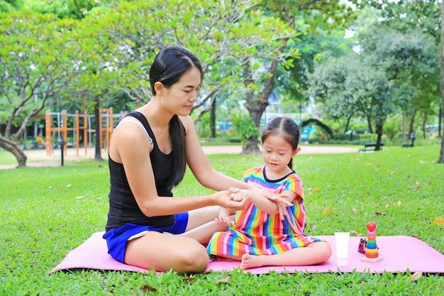 Bemuttern sie appying körperlotion für tochter im sommerpark. Premium Fotos