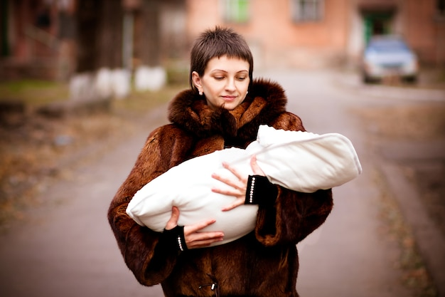 Bemuttern sie das halten des babys auf den armen, eingewickelt in einer decke. weichzeichnungseffekt. Premium Fotos