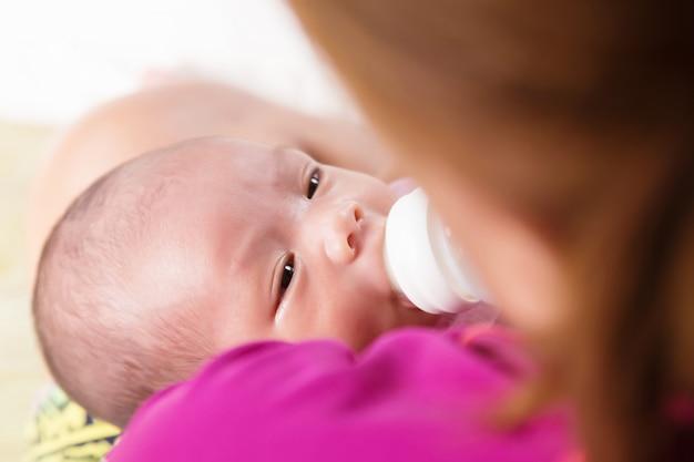 Bemuttern sie die fütterung des neugeborenen babys mit milch in der saugflasche. Premium Fotos