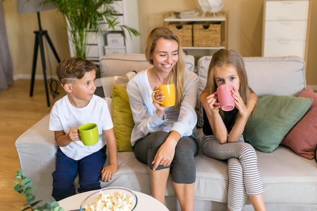 Bemuttern sie und ihre kinder, die auf einer vorderansicht der couch sitzen Kostenlose Fotos