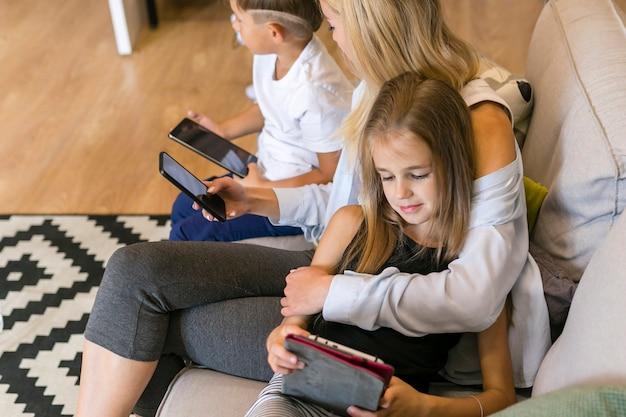 Bemuttern sie und ihre kinder, die ihre hohe ansicht der telefone betrachten Kostenlose Fotos