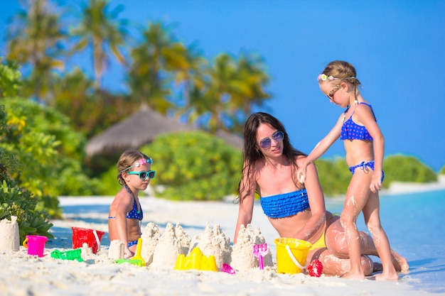 Bemuttern sie und zwei kinder, die mit sand auf tropischem strand spielen Premium Fotos