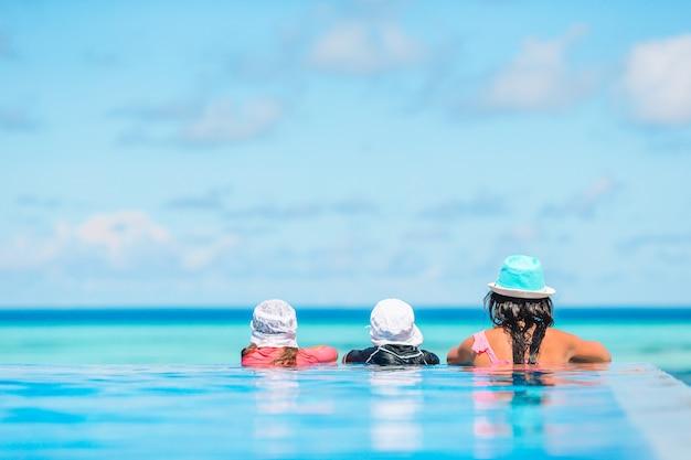 Bemuttern sie und zwei kinder, die sommerferien im luxusswimmingpool genießen Premium Fotos