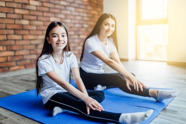 Bemuttern sie unterrichtende tochter, wie man in der yogaschmetterlingshaltung zu hause sitzt. sonnenlicht. Premium Fotos
