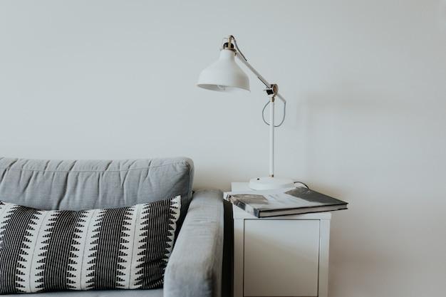 Bequeme couch in einem modernen haus mit einer lampe auf einem kleinen weißen regal und einem buch mit wasserfall Kostenlose Fotos