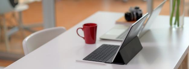 Bequemer schreibtisch mit laptop, digitalem tablet, becher, kamera, büromaterial und dekoration Premium Fotos