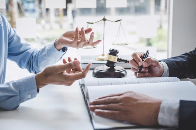 Beratung und konferenz der männlichen rechtsanwälte und der berufsgeschäftsfraufunktion und -diskussion, die an der anwaltskanzlei im büro haben. rechtsbegriffe, richterhammer mit waage der gerechtigkeit Premium Fotos