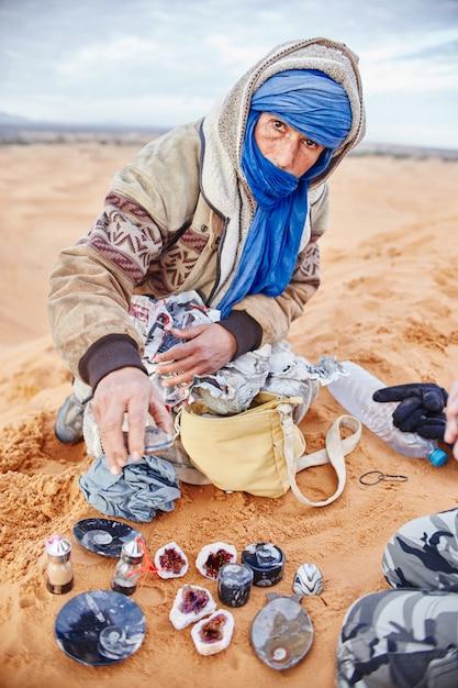 Berbermann in der sahara bietet eigene souvenirs und edelsteine an Premium Fotos