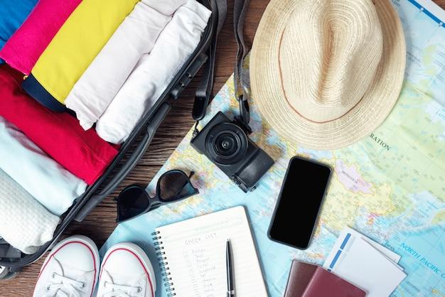 Bereiten sie zubehör und reiseartikel für eine neue reise vor und packen sie ihre kleidung in der koffertasche auf holzbrett Premium Fotos