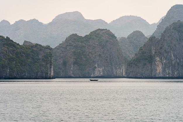 Berge der halong-bucht mit einem boot auf dem wasser Premium Fotos