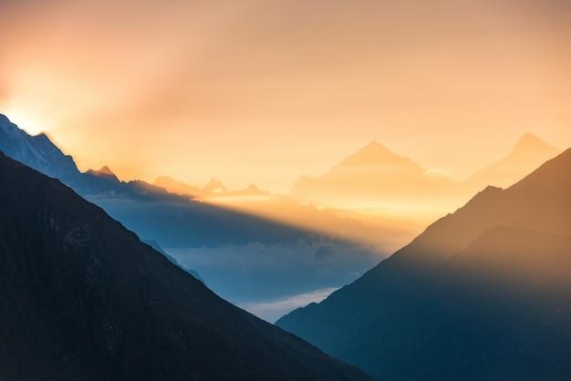 Berge und niedrige wolken bei buntem sonnenaufgang in nepal Premium Fotos