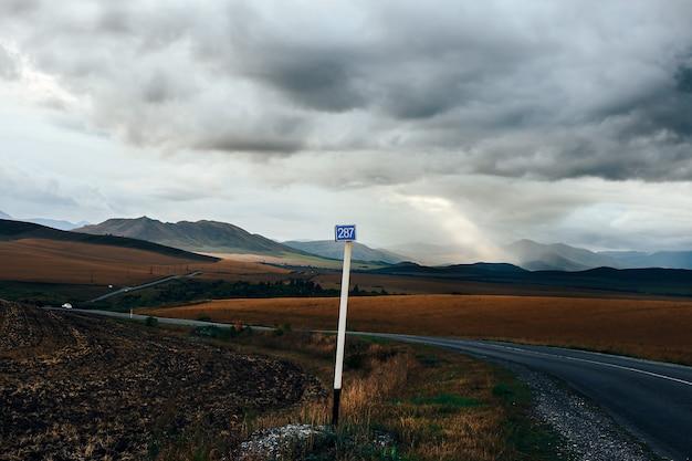 Bergpanorama mit einem feld und einem wolkigen himmel mit licht der sonne Premium Fotos
