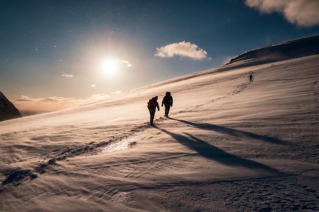 Bergsteiger mit dem rucksack, der auf schneebedecktem berg klettert Premium Fotos