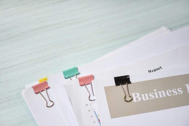 Bericht in papierform mit finanzieller büroklammer und geschäftsbericht Premium Fotos