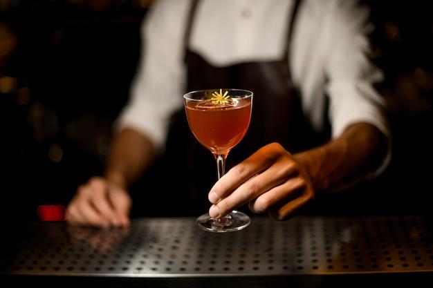 Berufsbarmixer, der ein cocktail im glas mit einer kleinen gelben blume dient Premium Fotos