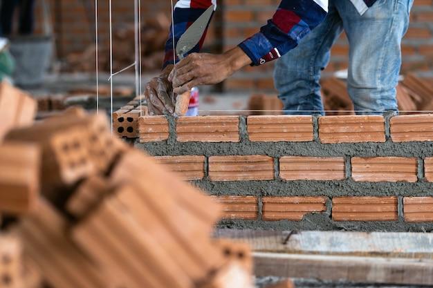 Berufsbauarbeiter der nahaufnahme hand, der ziegelsteine in neue industrieanlage legt Premium Fotos