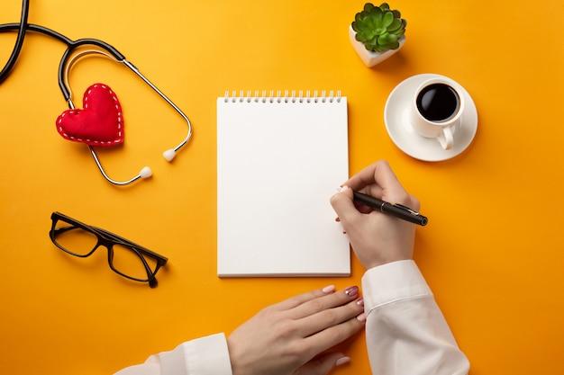 Berufsdoktor, der krankenblätter in ein notizbuch mit stethoskop, kaffeetasse, spritze und herzen schreibt Premium Fotos