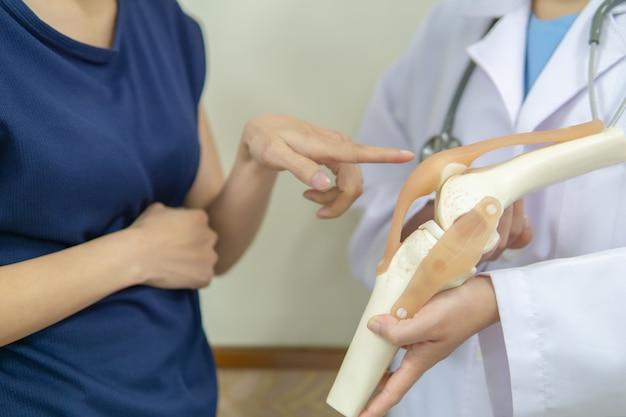 Berufsdoktor gibt einem weiblichen patienten eine stelle mit einer schmerz im knie. Premium Fotos