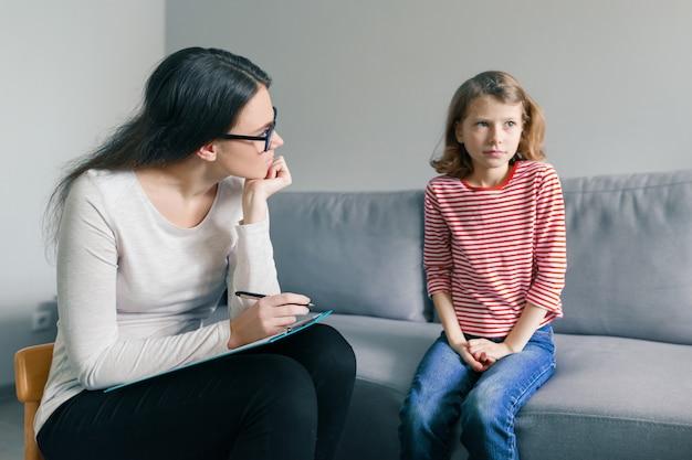 Berufskinderpsychologe, der mit kindermädchen im büro spricht Premium Fotos