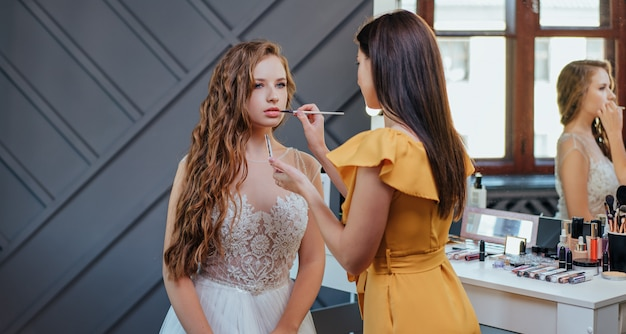 Berufsmake-up- und frisurenkünstler, der make-up für die braut macht. professionelle kosmetik Premium Fotos