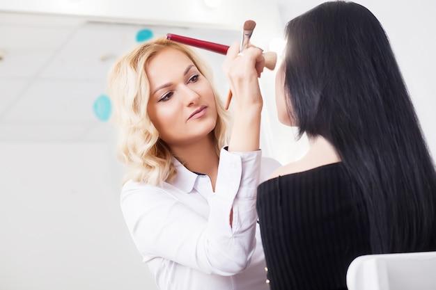 Berufsmaskenbildner, der mit schöner junger frau arbeitet Premium Fotos