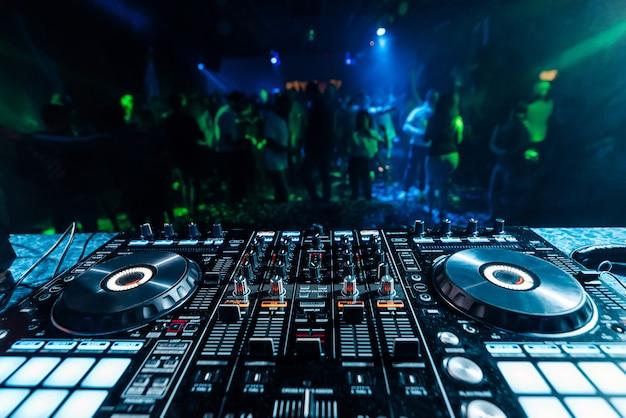 Berufsmusik dj-mischer in einem stand in einem nachtklub auf dem hintergrund von unscharfen schattenbildern von tanzenleuten Premium Fotos