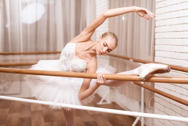Berufstänzer probt nahe ballettstange. Premium Fotos