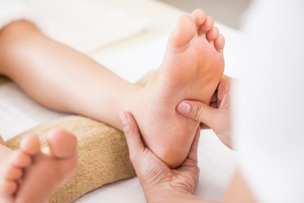 Berufstherapeut, der einer frau im badekurort thailändische fußmassage der reflexzonenmassage gibt Premium Fotos