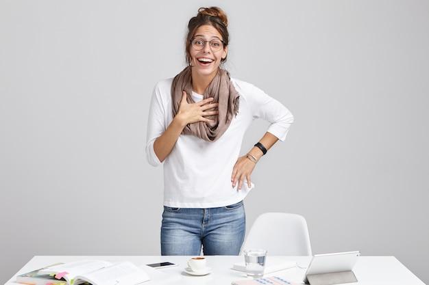 Berufung und kreativität. fröhliche junge erfolgreiche talentierte designerin, die schal und brille stehend trägt Kostenlose Fotos