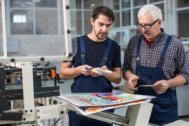 Beschäftigte druckereiarbeiter, die an gedruckten seiten stehen und farben für den nächsten druck auswählen Premium Fotos