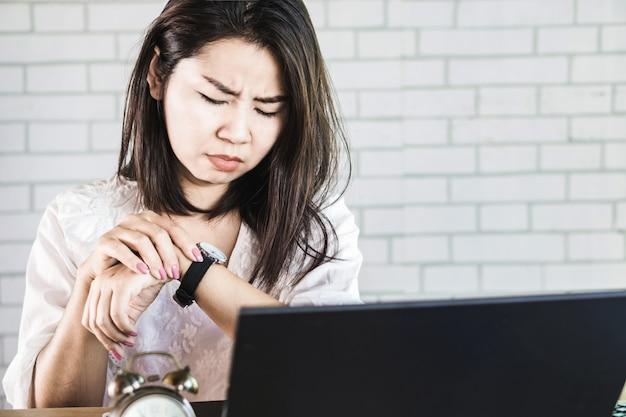 Beschäftigte geschäftsfrau, welche die zeit auf ihrer uhr überprüft Premium Fotos