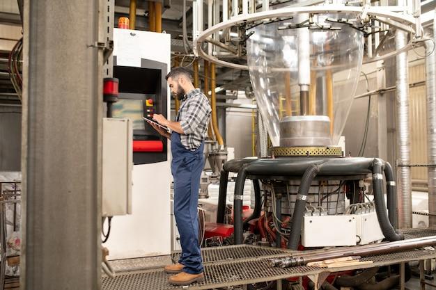 Beschäftigter junger ingenieur der polymerproduktionsfabrik, der durch bedienfeld steht, während technische daten in tablette durchgesehen werden Premium Fotos